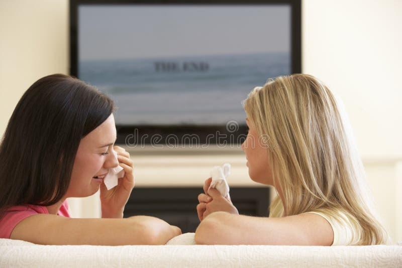 Två kvinnor som hemma håller ögonen på ledsen film på Widescreen TV arkivbild