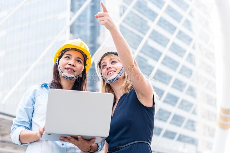 Två kvinnor som iscensätter granskning för start och lanserar nytt projekt Byggnads- och konstruktionsbegrepp Affär och lycka arkivbild