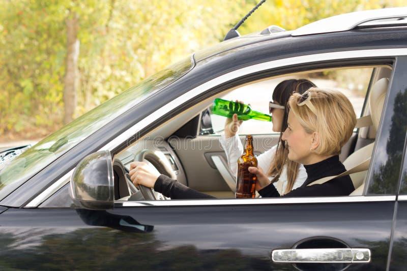 Två kvinnor som kör en bil, medan dricka royaltyfria foton