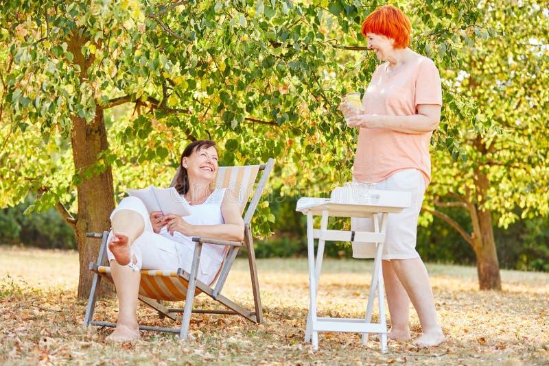 Två kvinnor som kopplar av i trädgården arkivbild