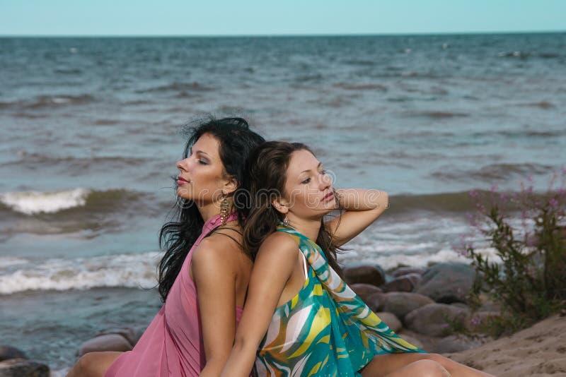 Två kvinnor som placerar på sand nära havet royaltyfria foton