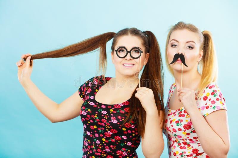Två kvinnor som rymmer karnevalaccessoies på pinnen arkivbild