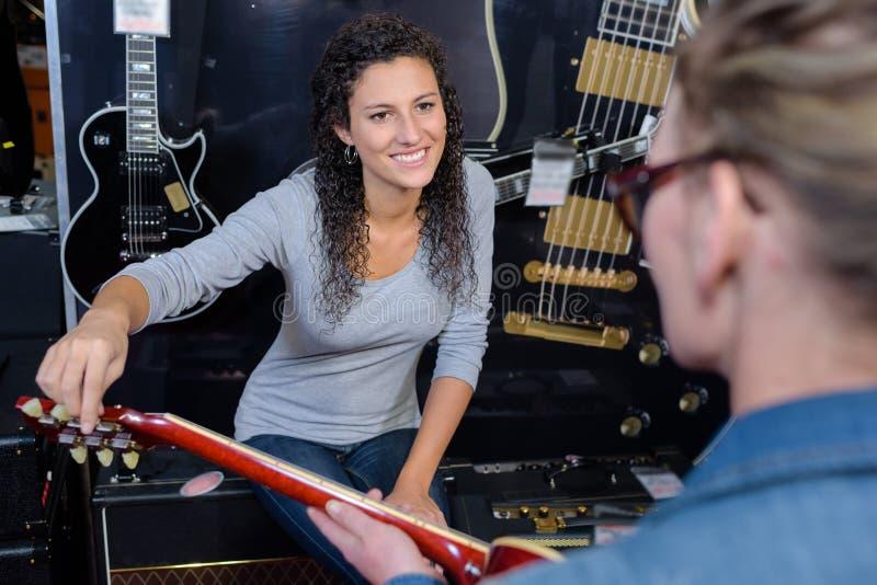 Två kvinnor som ser gitarren arkivfoto