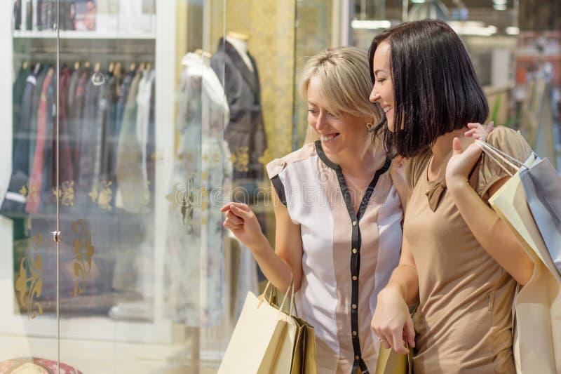 Två kvinnor som ser shoppar igenom, fönstret arkivbild