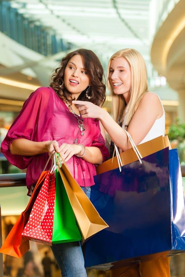 Två kvinnor som shoppar med påsar i galleria royaltyfri bild