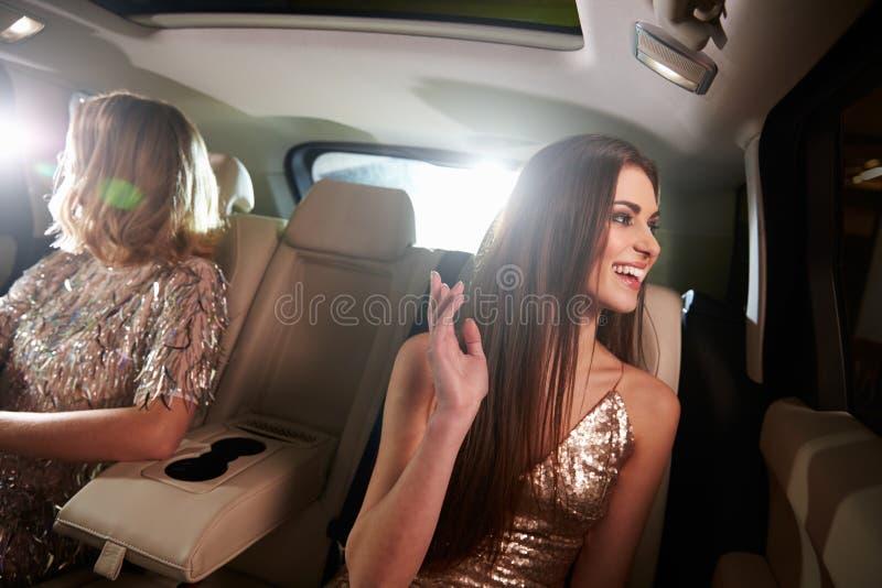 Två kvinnor som sitter i limo, ser ut ur fönster, i-bil sikt royaltyfria bilder