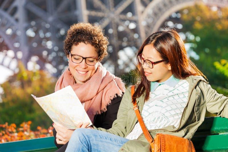 Två kvinnor som sitter på bänk med den pappers- översikten av Paris fotografering för bildbyråer