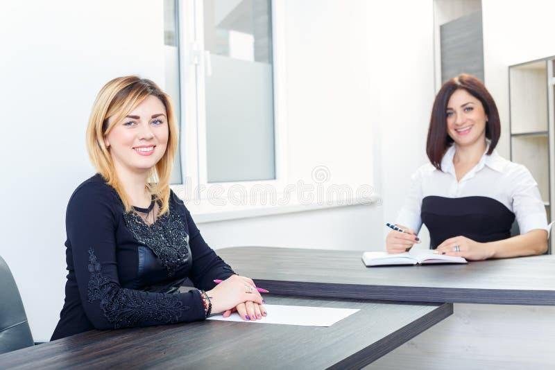 Två kvinnor som sitter på en tabell i kontoret Blondin och brunett på jobbintervju eller möte royaltyfri bild