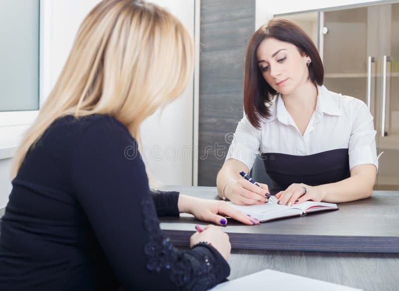 Två kvinnor som sitter på en tabell i kontoret Blondin och brunett på jobbintervju eller möte royaltyfri foto