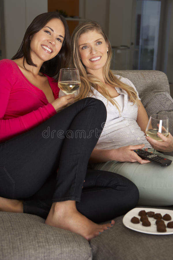 Två kvinnor som sitter på Sofa Watching TV som dricker vin royaltyfri bild