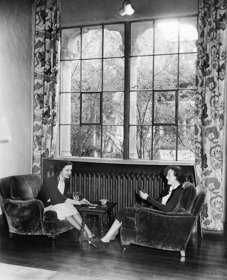 Två kvinnor som spelar kort och tillsammans sitter (alla visade personer inte är längre uppehälle, och inget gods finns Leverantö royaltyfri foto