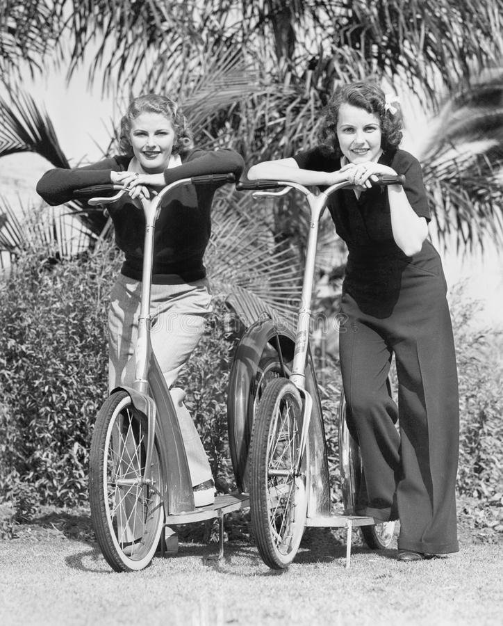 Två kvinnor som står på deras sparkcyklar (alla visade personer inte är längre uppehälle, och inget gods finns Leverantörgarantie arkivbild