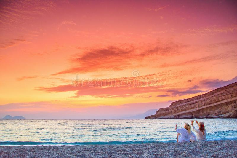 Två kvinnor som tar foto av den fantastiska solnedgången på stranden av Matala, Kreta arkivbild