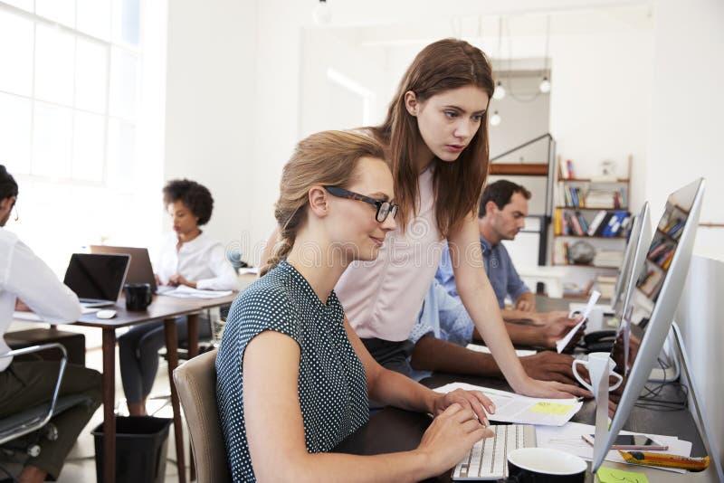 Två kvinnor som tillsammans arbetar på datoren i öppet plankontor royaltyfri bild