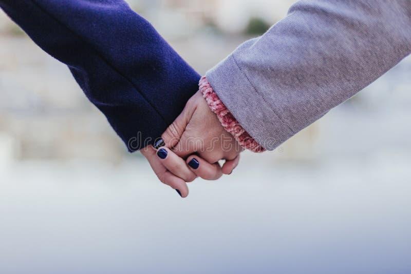 Två kvinnor som utomhus rymmer händer man för begreppskyssförälskelse till kvinnan vänner eller systrar arkivbilder