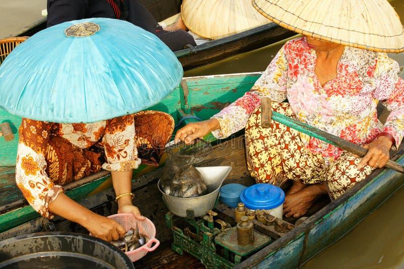 Två kvinnor som väger och säljer den nya fisken på en sväva marknad royaltyfri foto
