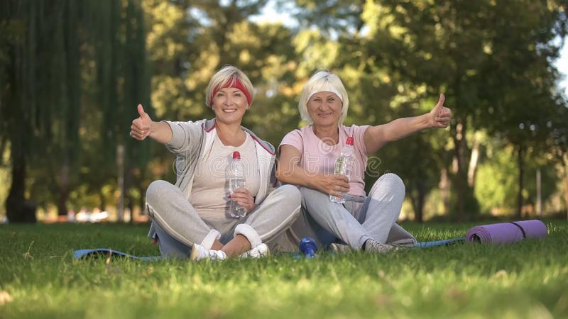 Två kvinnor som visar tummar upp att sitta på gräs, når att ha gjort övningar, realitet royaltyfri foto