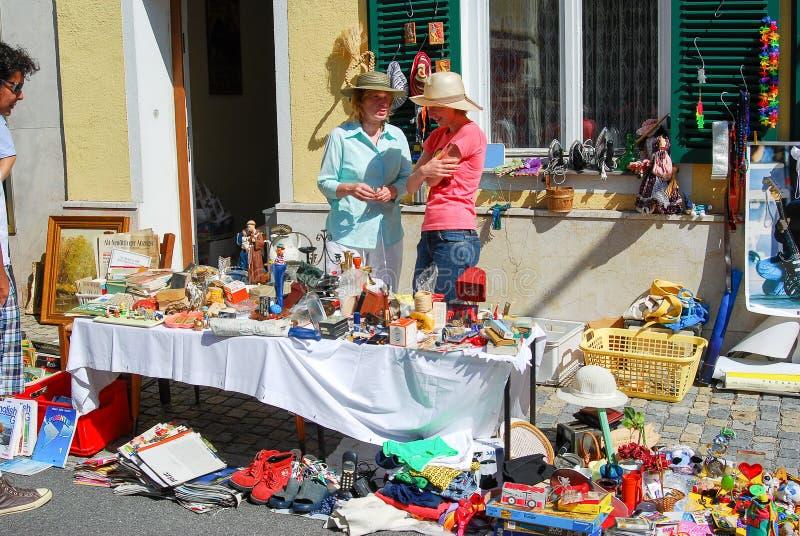 Två kvinnor står bak en tabell som säljer använda artiklar fotografering för bildbyråer