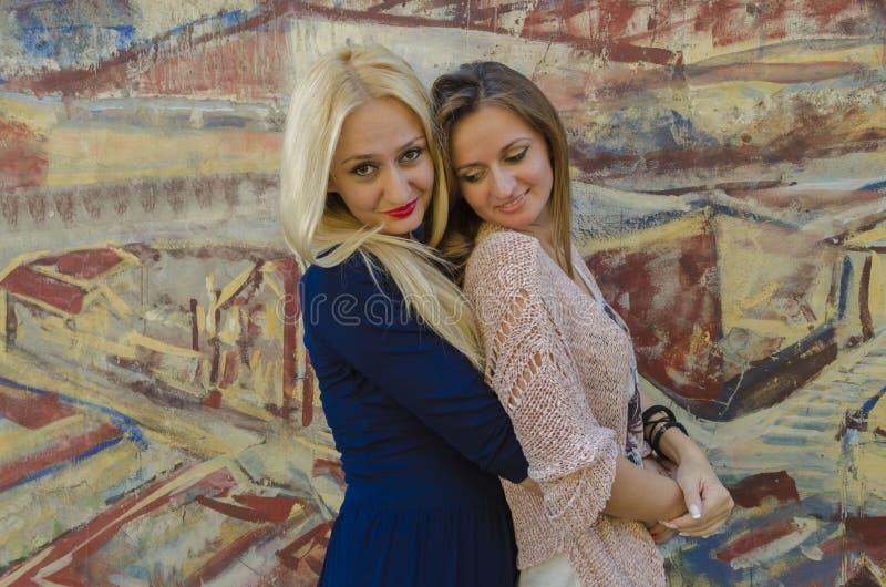 Två kvinnors systrar nära bilden med den målade grafiten arkivfoto