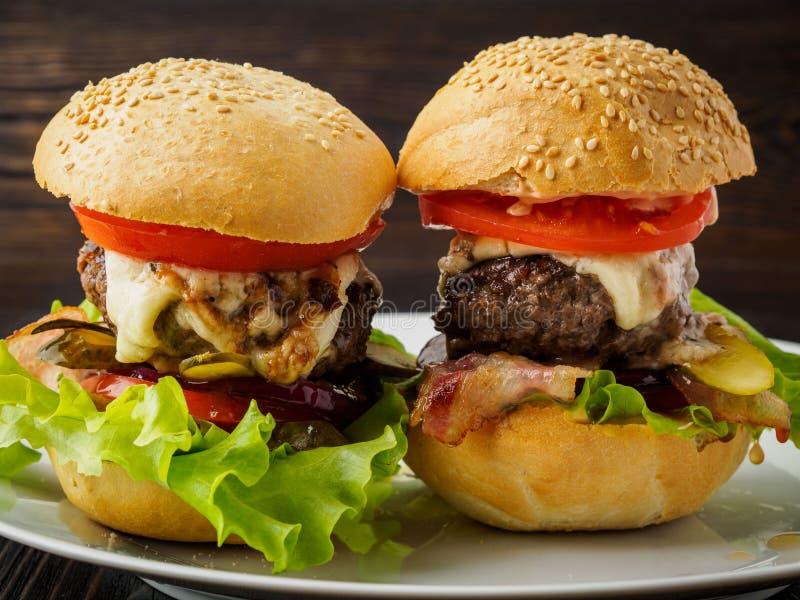 Två läckra hemlagade hamburgare med nötköttkotletten, ost, onio arkivbilder