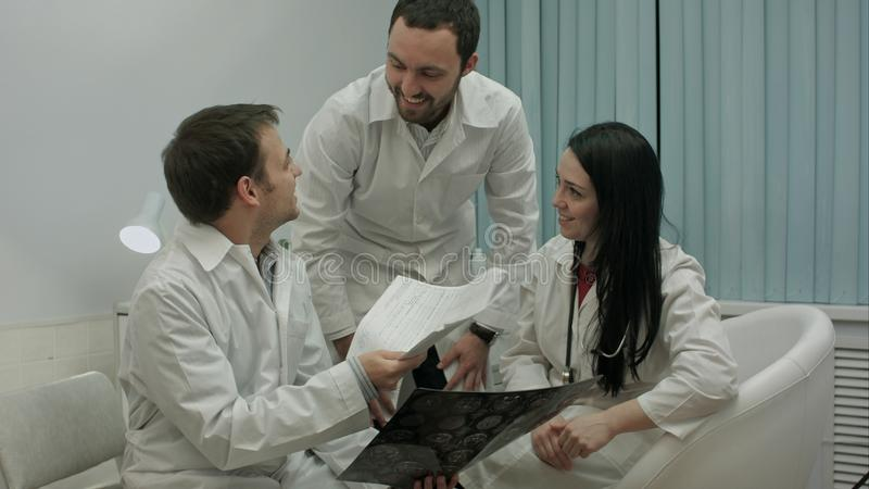 Två läkare som kontrollerar tålmodig ` s, head scanning, då kommer läkaren med röntgenstrålen för goda nyheter härom royaltyfri bild