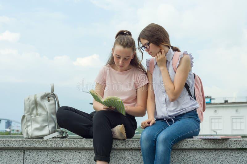 Två lärande flickastudenter med ryggsäckar och läroböcker som är utomhus- i en parkera arkivfoton
