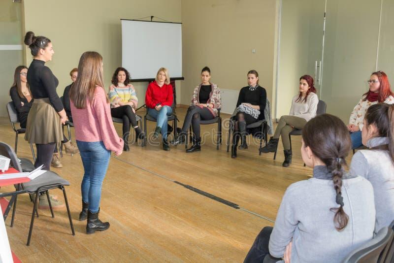 Två lärare och grupp av unga studenter som har en gruppdiskussion i det stora klassrumet och sitter i en cirkel på stolar royaltyfria bilder