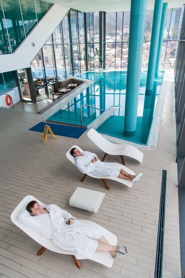 Två lögner för ung man på en dagdrivare i en simbassäng i en vitt kappa och koppla av för frottédressing royaltyfri bild
