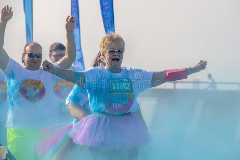 4 - 6 - 2019 - två löpare - på en pensionärkvinna i en ballerinakjol och en bli skallig man bak hennes - rymmer upp deras armar,  fotografering för bildbyråer