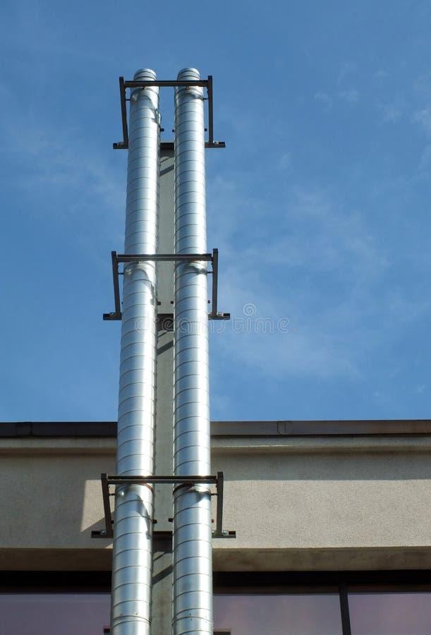 Två lampglas för extraktion för skinande stålmetall industriella på sidan av en byggnad mot en blå sommarhimmel med solljus och s arkivfoto
