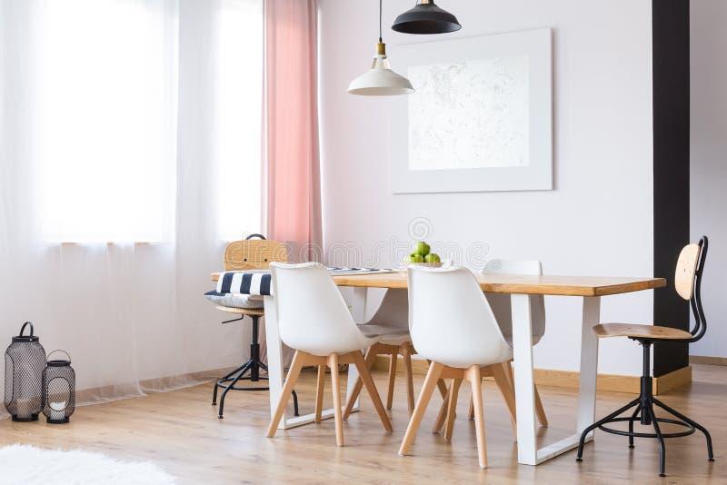 Två lampor som hänger över tabellen fotografering för bildbyråer