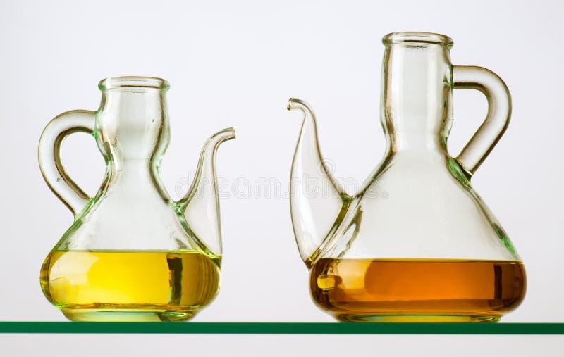 Två lantliga crystal oljekannor med olja på hylla royaltyfri fotografi
