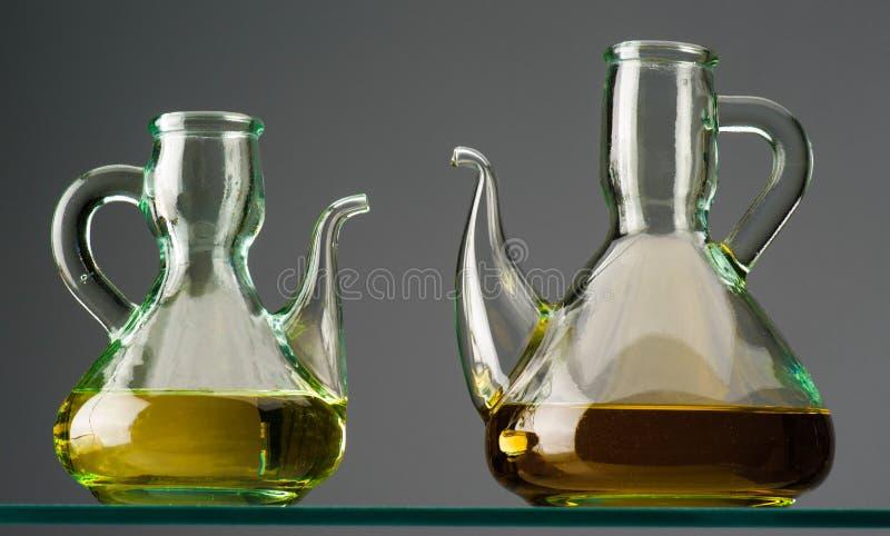 Två lantliga crystal oljekannor med olja på hylla royaltyfria foton
