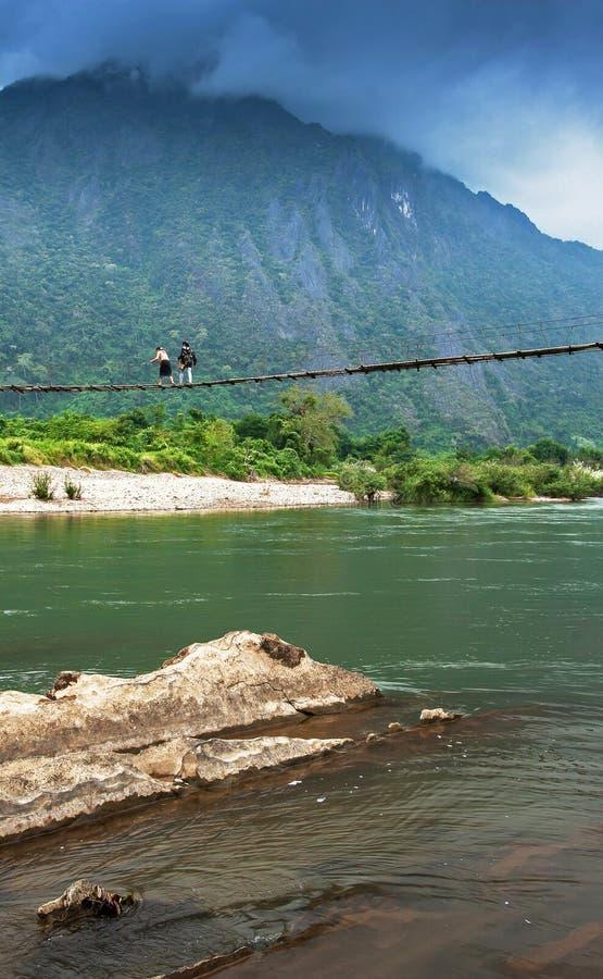 Två Laos flickor som går över upphängningbron över Nam Song River, den fantastiska molnig och bergskedjabakgrunden arkivfoto