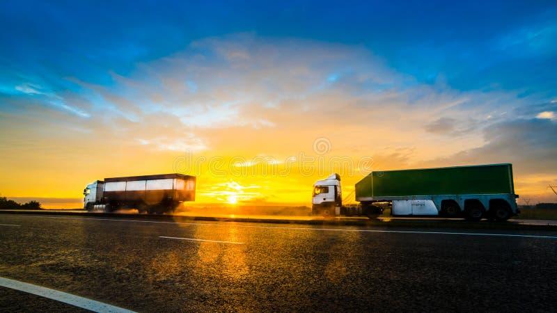 Två lastbilar på huvudvägen i rörelsesuddighet på solnedgången royaltyfria bilder