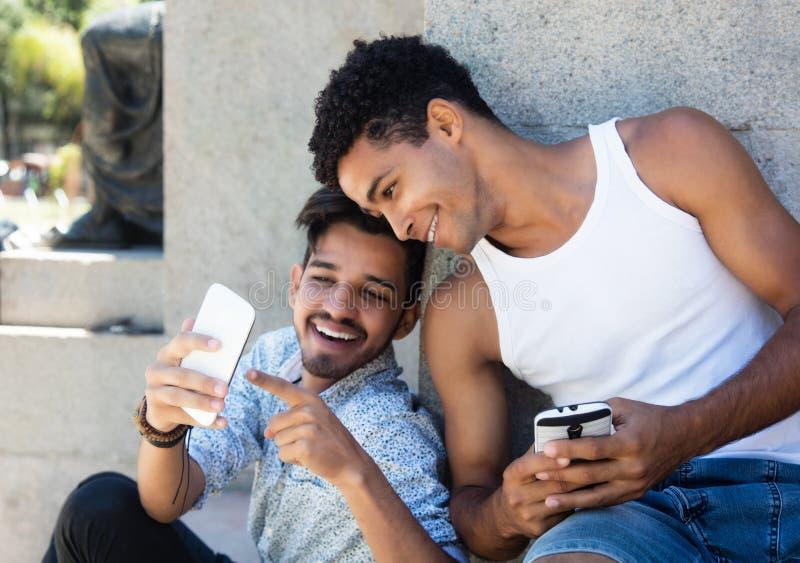 Två latin - amerikanska grabbar som spelar en lek med telefonen royaltyfria bilder