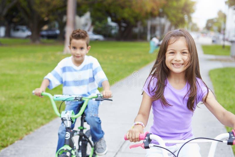 Två latinamerikanska barn som rider cyklar parkerar in royaltyfri bild