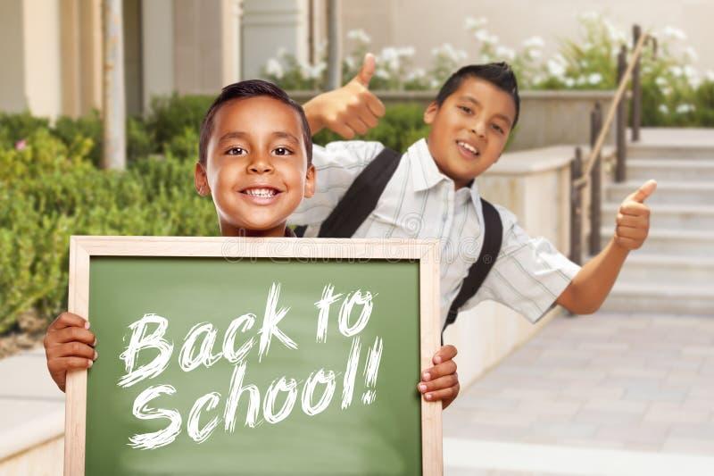 Två latinamerikanska pojkar som tillbaka ger tummar upp hållande till skolakritabrädet royaltyfria bilder