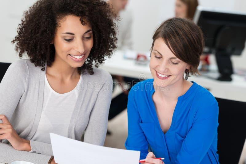 Två le affärskvinnor som arbetar på ett dokument royaltyfri bild