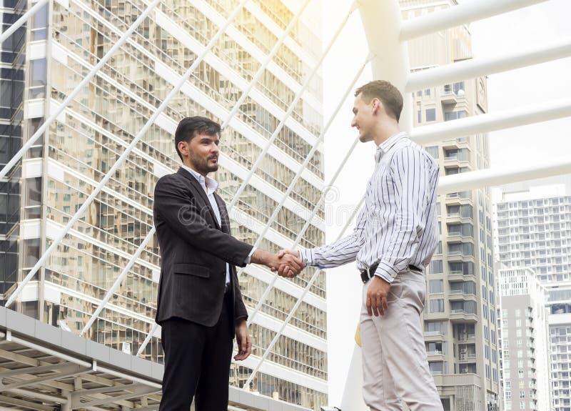 Två le affärsmän som tillsammans skakar händer arkivfoton