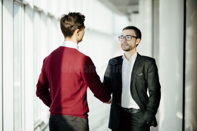 Två le affärsmän som tillsammans skakar händer, medan stå vid fönster i en kontorsstyrelse som förbiser staden royaltyfri fotografi