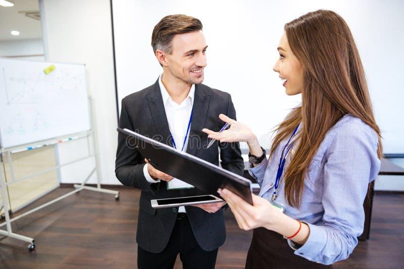 Två le businesspeople som tillsammans talar och arbetar arkivbilder