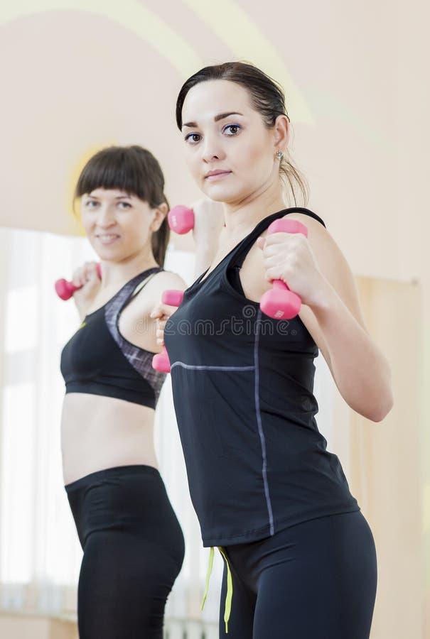 Två le Caucasian sportkvinnor som övar med skivstånger fotografering för bildbyråer