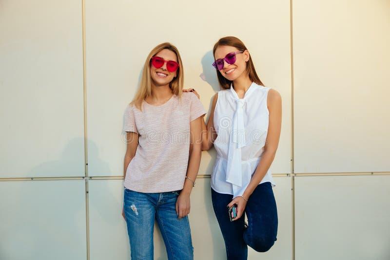 Två le flickor som poserar på kameran, utomhus royaltyfri foto