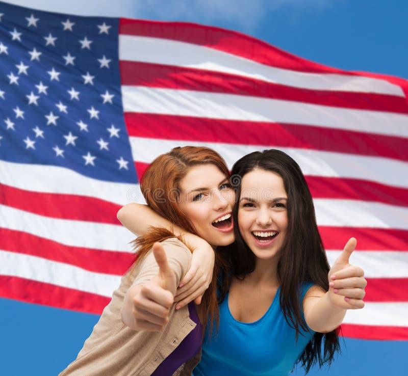 Två le flickor som visar upp tummar royaltyfria foton