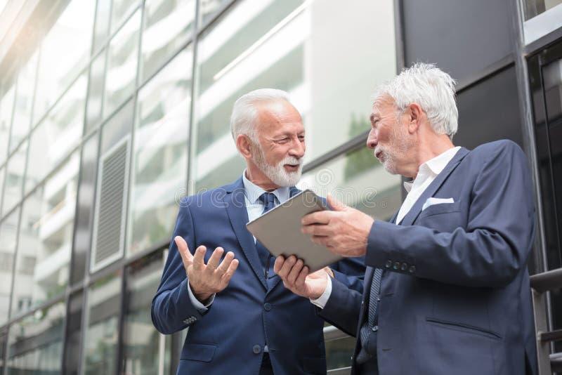 Två le höga affärsmän som arbetar på en minnestavla och diskuterar arkivfoton