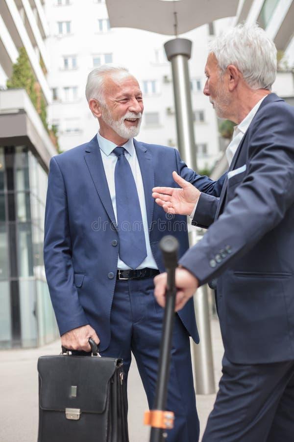 Två le höga affärsmän som möter och talar på trottoaren som omges av kontorsbyggnader arkivbilder