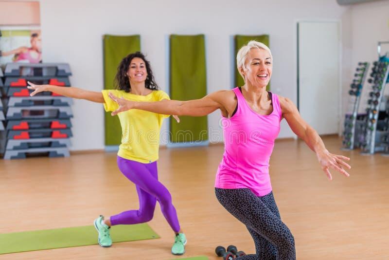 Två le idrotts- kvinnor som gör aerobisk dans, övar att rymma deras armar sideward inomhus i konditionmitt royaltyfri foto