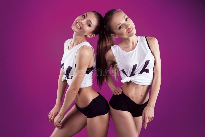 Två le konditionunga flickor på rosa bakgrund arkivbilder