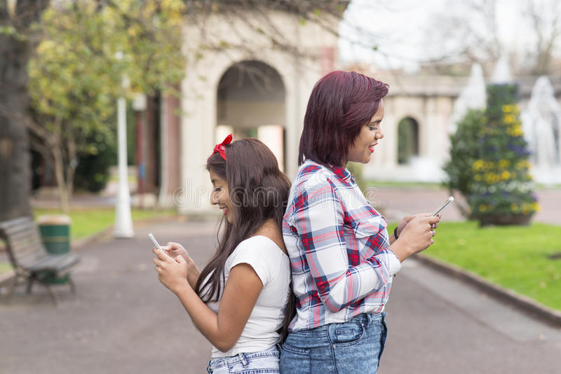Två le kvinnavänner med den smarta telefonen i parkera arkivfoton